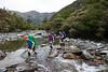Three female trampers cross stream, Griffin Creek, Kelly Range Styx River Area