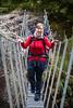 Female tramper crossing Kokatahi swing bridge, Kokatahi Stream