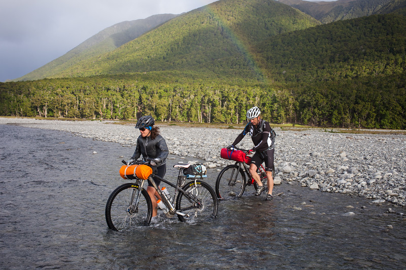 Two mountain bikers (male, female) crossing stream with rainbow, Lake Sumner Forest Park