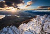 The sun sets behind Queenstown and the Wakatipu Basin on a winter afternoon. From Queens Drive, West Face of the Remarkables. Otago