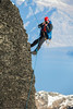 A male climbing photographer hanging on a rope on the side of a cliff, Remarkables, Queenstown