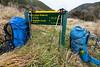 Two backpacks & walking poles beside sign, St James Conservation Area