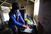 Female tramper adjusts stove inside Rokeby Hut, St James Conservation Area
