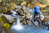 Woman tramping past stream in the Spenser Mountains, St James Conservation Area