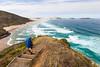 Female tramper (40's) walks Te Araroa Trail. Werahi Beach and Cape Maria van Diemen in background
