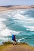 Female tramper (40's) standing above breaking surf. Werahi Beach and Cape Maria van Diemen in background