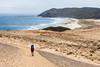Female tramper (40's) walks Te Araroa Trail over Herangi Hill. Werahi Beach and Cape Reinga in background