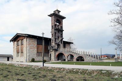09 Plečniks origineller Kirchenbau in Barje zeichnet sich durch die lange, auf Rundbögen gestützte Eingangstreppe und den offenen Kirchturm vor dem einfachen Gebetssaal aus.