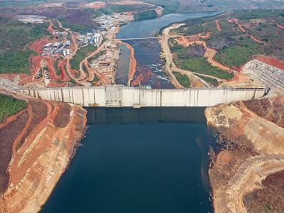 08 Souapiti, Guinea.  Am seit 2015 im Bau befindlichen Souapiti-Staudamm am Konkouré-Fluss zeigen sich wie im Brennglas die Widersprüchlichkeiten des Fortschritts in Afrika: Einerseits soll das von chinesischen Staatsfirmen finanzierte und realisierte Megaprojekt mit geschätzten Kosten von zwei Milliarden US-Dollar die Elektrifizierung des westafrikanischen Landes entscheidend voranbringen und dank seiner Leistung von 450 Megawatt die häufigen Stromausfälle in der 220 Kilometer westlich gelegenen Hauptstadt Conakry reduzieren. Andererseits müssen über Hundert Dörfer dem entstehenden 250-Quadratkilometer-Stausee weichen. Ob deren mehr als 16.000 umzusiedelnden Bewohner – vor allem Bauern, die dadurch ihrer Lebensgrundlage beraubt wurden – ausreichend oder überhaupt kompensiert werden ist derzeit mehr als fraglich. | The Souapiti hydroelectric dam, which is being built since 2015 at the Konkouré river, magnifies the contradictions of progress in Africa: on the one hand the US$ 2bn megaproject with its output of 450 MW of electricity that is financed and being constructed by Chinese state companies will decisively advance the electrification of the West African country and help reduce the number of power cuts that affect the capital city of Conakry, some 220 km to the west of the project. But more than one hundred villages will have to make way for the resulting 250 sq km reservoir. It is currently more than unclear if the 16,000-strong local population who have to be resettled - mainly farmers, who will lose their only source of income - will receive adequate compensation, or any at all.