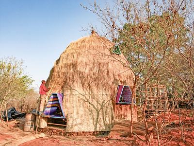 06 Chaseyama, Simbabwe | Chaseyama, Zimbabwe. Radikal lokal: Für das Pilotprojekt eines Kindergartens in der Provinz Manicaland, entworfen von der deutschen Architektin Anna Heringer, wurden konsequent nur örtlich verfügbare Materialien verwendet. Entstanden ist ein kindgerecht verspielter und fröhlicher Bau, errichtet in enger Zusammenarbeit mit lokalen Handwerkern. Auf dem massiven Steinsockel steht eine markante Holz-Skelett-Struktur, die der örtlichen Bautradition entsprechend mit Stroh gedeckt ist. Neben dem zentralen Raum bietet der Kuppelbau den Kindern unterschiedlich große Nischen und Alkoven zum Spielen oder Zurückziehen, deren trapezförmige Holzrahmen den Ausblick farbenfroh rahmen. | Radically local: the pilot project of a kindergarten in the province of Manicaland, designed by the German architect Anna Heringer, saw the consequent use of locally sourced materials. The result is a playful and cheerful, child-adequate building that was erected in close collaboration with local craftsmen. A striking wooden supporting structure which is covered in straw stands on a massive stone base, in accordance with local building traditions. Apart from the central internal space the domed structure offers the children niches and alcoves of different sizes which they can play in or retreat to. The trapezoid wooden frames of these niches colourfully frame the children's view towards the outdoors.