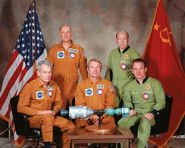 """The principal crews of the Soyuz-19 and Apollo spaceships. Seated (left to right): astronauts D. Slayton and B. Brand and cosmonaut V.N. Kubasov. Standing (left to right): astronaut T. Stafford and cosmonaut A.A. Leonov. On the cosmonauts' training suits we can clearly see the 'Balashova' patch, which was worn by all crews (both principal and back-up crews) during training for the space flight. Photo: NASA.Mannschaften der Sojus-19 und Apollo Missionen. Sitzend (links nach rechts): Astronauten D. Slayton und B. Brand und Kosmonaut V.N. KubasovStehend: (links nach rechts): Astronaut T. Stafford und Kosmonaut A.A. LeonovAuf den Trainingsanzügen können wir das """"Balashova""""-Abzeichen klar erkennen, das während des Trainings für die Mission sowohl von den Haupt- wie auch den Reservemannschaften getrategen wurde.Foto: NASA"""