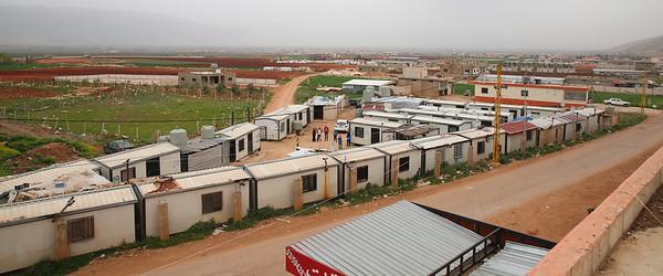 Dieses Containerdorf In der Nähe der Ortschaft Qaraoun an der syrischen Grenze besteht seit 2010 und entwickelt sich langsam zu einem eigenen Ortsteil. Im Hintergrund entstehen weitere Plastikzelte. Über kurz oder lang wird sich das Lager erweitern. Bild: © Wajiha Shihab