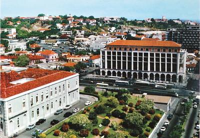 Bild 10: Luanda, Finanzbehörde, um 1962. Das staatliche Gebäude am Largo Almirante Baptista de Andrade (heute Largo de Mutamba) entstand im Auftrag des Amts für Städtebau der Überseeprovinzen 1953 nach Plänen von João António de Aguiar. Vor dem Gebäude erstreckt sich ein grüner Platz, links erhebt sich das Rathaus von Luanda.