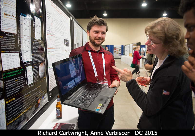 Richard Cartwright (APL) tries to impress Anne Verbiscer with his plots of the 2.2-micron Uranian satellite dark material distribution.<br /> <br /> Credit: Henry Throop<br /> Oct 2015<br /> DPS47 National Harbor