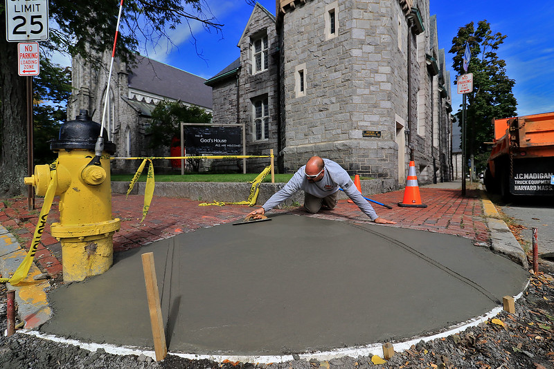 Fitchburg DPW heavy equipment specialist Randy Duvel finishes up rebuilding a handicap ramp at the corner of Fox and Main street on Thursday morning.  SENTINEL & ENTERPRISE/JOHN LOVE