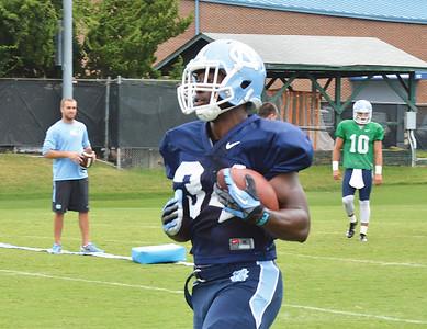 Elijah Hood runs down the field during a practice pass play.