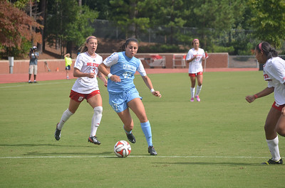 UNC's Alex Kimball (47) dribbles past NC State's Jenna Kalwa (3) in Sunday's game against NC State University.  The Lady Tar Heel's won 2-1 against the Lady Wolfpack.