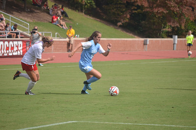 UNC's Sarah Ashley Fristenberg (54) dribbles past NC State's Jenna Kalwa (3) in Sunday's game against NC State University.  The Lady Tar Heel's won 2-1 against the Lady Wolfpack.