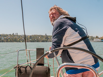 Jess, down lit by the sun, holding the the sail during a strong wind. Photo by Chris Grimshaw photo 235