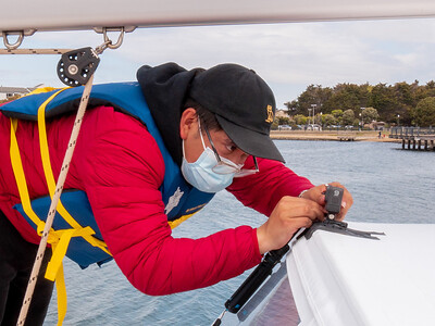 Cesar prepping a GoPro at the bow of the boat. He'll typically have three or four cameras running at once to grab as many angles as possible. Photo taken in Richmond, CA by Chris Grimshaw