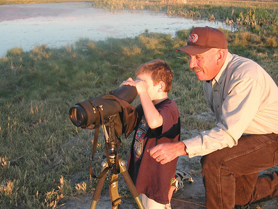 Phil Douglass, conservation outreach manager for the northern region, helps a child use a spotting scope to view wildlife.  Photo by Utah Division of Wildlife Resources.
