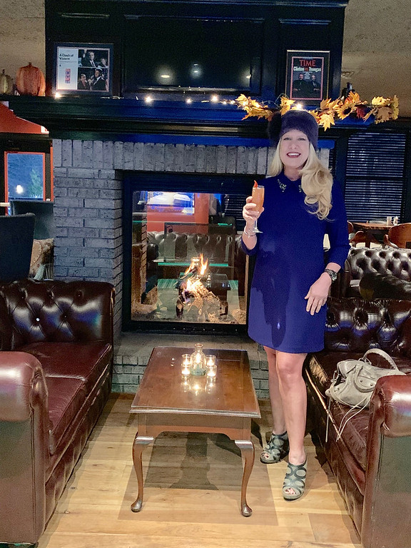 . A toast by the fire: Feeling warm and toasty by the fire!! I�m wearing a deep-purple Vince Camuto cocktail dress with jewels around the collar, a purple rabbit-fur hat, a pair of gray Via Spiga ankle boots and a gray Balenciaga pocketbook! A huge thank-you to the Stonehedge team who were just outstanding in making this specialty signature champagne cocktail, catering to all of the guests, making the event extra-special and taking this picture!