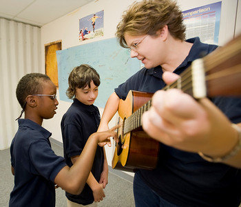 Justin Wilborn (left) helps Heidi Thurmond, lead instructor for Vivo, play a song on the guitar, while Worthy deQuilettes waits patiently for his turn.
