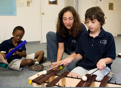 Tracee Prillaman (center), an instructor for Vivo, watches Worthy deQuilettes (right) strike up a tune in two octaves on the xylophone, while Justin Wilborn provides background rhythm with a mallet.