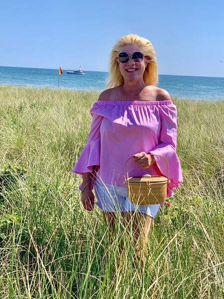 The Z-List  holds the traditional Nantucket basket pocketbook on Siasconset Beach (known as Sconset to the locals).