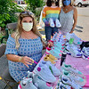 Angelina Tavares signs sneakers for Kaylie Petullo and Jody Bue of Groton. Jody donated a slew of homemade masks to the endowment.
