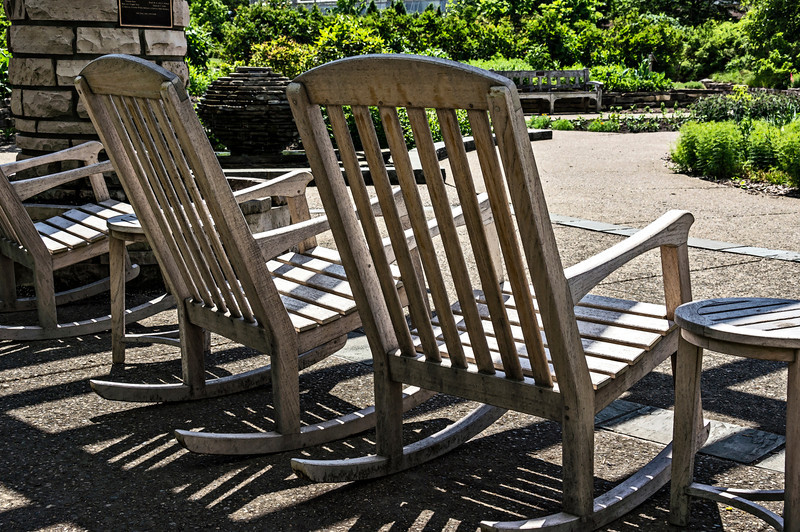 Off their rockers.<br /> These large, comfortable rockers, conveniently situated in the pavilion of the Gateway Garden, rarely have people seated in them.  People are missing a good thing!  You can bring a book, and maybe a cool drink, sit, rock, listen to the plash of water in the fountains and the songs of the birds, enjoy the colorful flowers.  What are they waiting for?<br /> <br /> DP170-2013  Posted June 19; processed ditto.<br /> (A layer of poster edges over fresco, at reduced opacity, has been applied)<br /> .<br /> Matthaei Botanical Gardens, Ann Arbor, Michigan<br /> June 13, 2013