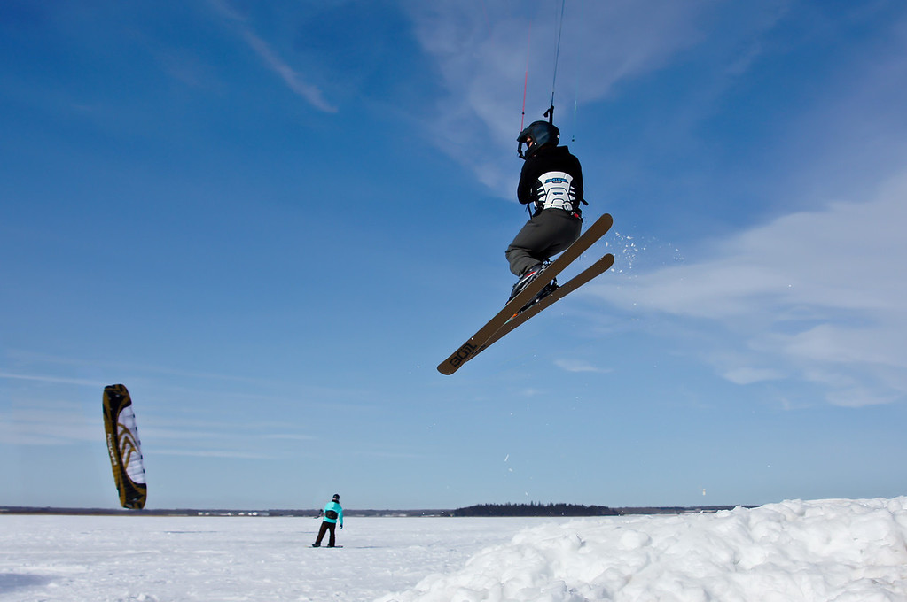 """072 Mar 12/12 A few hundred feet away from where I take my Aurora pictures a kite skiing/boarding group was having a meet.  Apparently the winds were not good enough for great jumps but good enough for me to get a few shots.  Thanks for the comments about the picnic tables.  I think the reason they are stacked like this is so the snow and ice does not accumulate on the tops and help rot the wood.  During a """"normal"""" winter these tables would be sitting in snow a couple of feet deep at this time of year."""