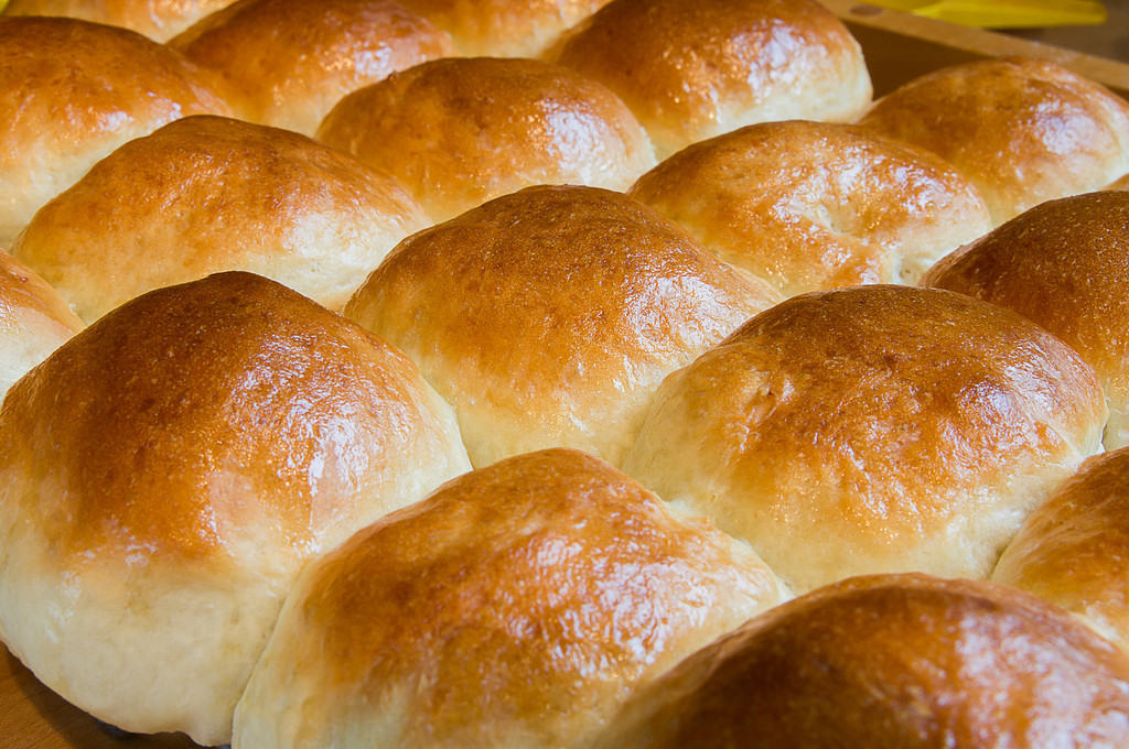 126 Sep 3/12 Baking buns.  The weather yesterday was rain and gloom so I thought it would be a good day to bake bread.  If I didn't know better I would think I'm nesting.  Critique always welcome and I'll go first.  As far as composition goes,  I like it.  It's one of my favorite food views.  Lighting is all wrong, the light source should be coming from 10:00 - 2:00 and I've got it about 4:00.  By simply turning the racks and the camera I would have changed the light.  The reflection of the light on the dark side is good, eliminating shadows.  I should have put up a screen between the light and the buns to help prevent the highlights from the melting butter from being blown out.  By changing the direction of the light, this may have solved the highlight problem.
