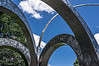 "Small Park with Arches 23<br /> Intersections<br /> <br /> DP219-2013  Posted August 7; processed ditto<br /> <br /> Artist:  Alice Adams.  Created 1984.  Originally clad in laminated wood.  The difficulty of maintaining the wood in Toledo's harsh climate necessitated it's eventual removal, and the refinishing of the underlying metal structure.<br />   <br /> More photos of this sculpture can be seen here, including ones which show it in its entirety:  <a href=""http://smu.gs/19NfwWN"">http://smu.gs/19NfwWN</a> <br /> <br /> Toledo Botanical Garden, Ohio<br /> July 24, 2013"