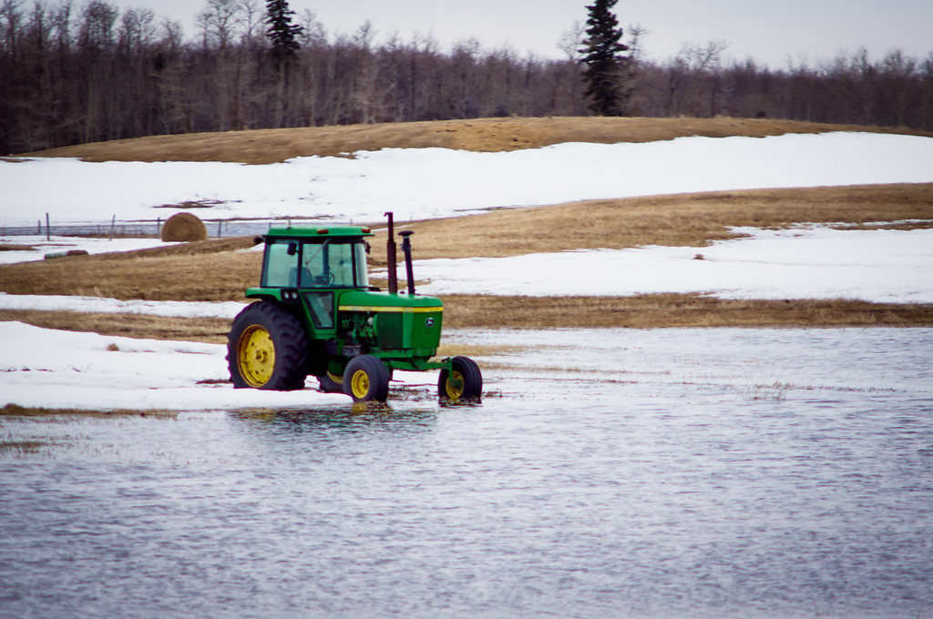 114 Apr 24/13 Taken during a drive by from the highway so the clarity is not where I'd like it to be.  This tractor has been sitting in a field all winter and now the water in the field is starting to take over.