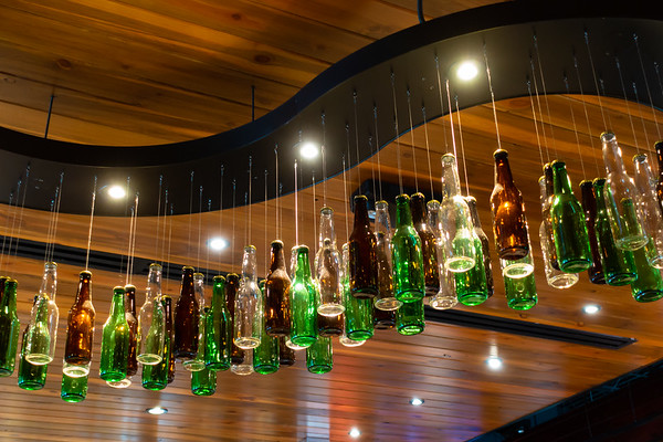 Empty bottles hanging from the ceiling at a restaurant.