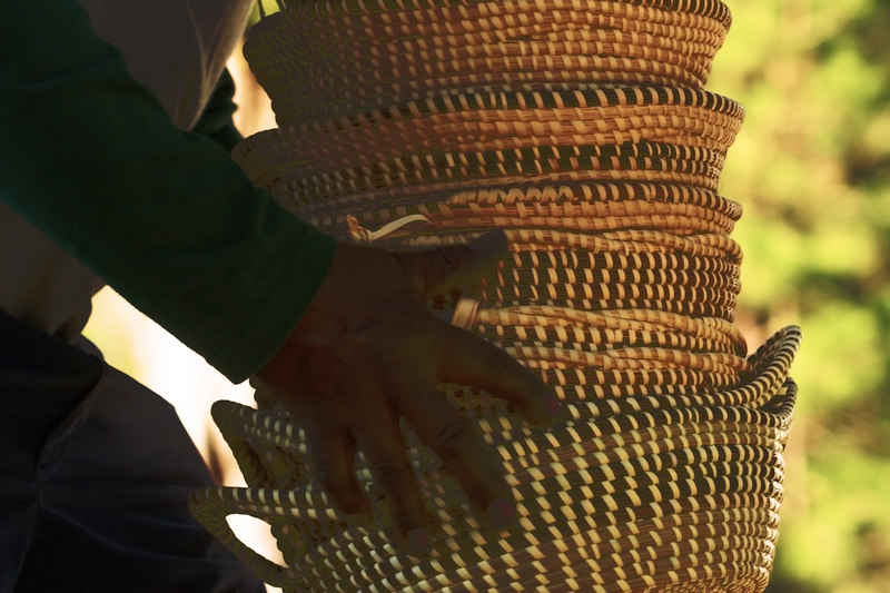 Sweetgrass Baskets<br /> 3/10/2007<br /> <br /> You all know about the sweetgrass baskets made from African culture in days of slavery, the art, and it is an art, is passed down in families to this day.<br /> <br /> Those of us who care hope that this art will never die.  It is becoming more difficult to find the materials in the marshes to make these baskets.  And the country roadsides where they have been sold for years, they have become highways.<br /> <br /> The man who is carrying these baskets back to his van, he told me much.  I wish I could have heard more.  He had a wealth of baskets (they are not cheap, after all, each is made with the same care as the ones that are displayed in the Smithsonian).  I asked if he had made them all, he said that he and his family had, I heard that.  They go all over the south selling the baskets.  The world is changing from the slow country roads outside of Mount Pleasant.<br /> The people who make the baskets are trying to adapt.  May they forever be able to find the grasses in the marsh (we talked about that part, but I could not hear what he said).<br /> <br /> ginger