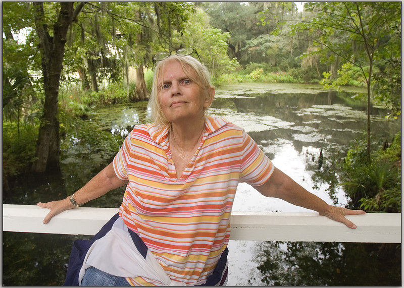 "Real Me: no make up, hair back and ""wet"", visible ""glow"", no computer shenanigans like removing under eye circles, none of that, just ME!<br /> <br /> On bridge at Magnolia Gardens, very near the Ashley River.  In the pond behind me I often find an egret.  He then goes (walks) to the other really pretty pond where I have taken many photos.  There are also alligators in that pond and whatever else one would expect.<br /> <br /> Bill took this picture, so I guess technically he is the photographer, but I was the producer and director.  Also, I played myself in this photo.<br /> <br /> Had miles to go, as the man said.<br /> <br /> ginger  (late today, sorry!)<br /> <br /> As an aside:  Have any of you ever forgotten that your glasses were on your head?<br /> I looked all over and thought I had dropped them in the water... with the gator!<br /> Looking there, it was certainly possible."