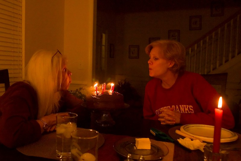 Photo courtesy of Bill<br /> <br /> Me and my daughter, Sara, blowing out candles on our mutual birthday cake (a day early, sun, birthday, today, mon, nov 20).  I turn 67, she turns 39.<br /> <br /> I shot without a flash, it looked ok, seemed like a good idea at the time, but Bill got the best shot right here.  I got much blur.  Here it is mostly grain, smile.<br /> <br /> Bad weather coming here, oh, boy... I want to get out and shoot.<br /> we might even get snow.  Hope I get up to Sara's again Thursday.  Nice time today, everyone is very tired!<br /> <br /> ginger