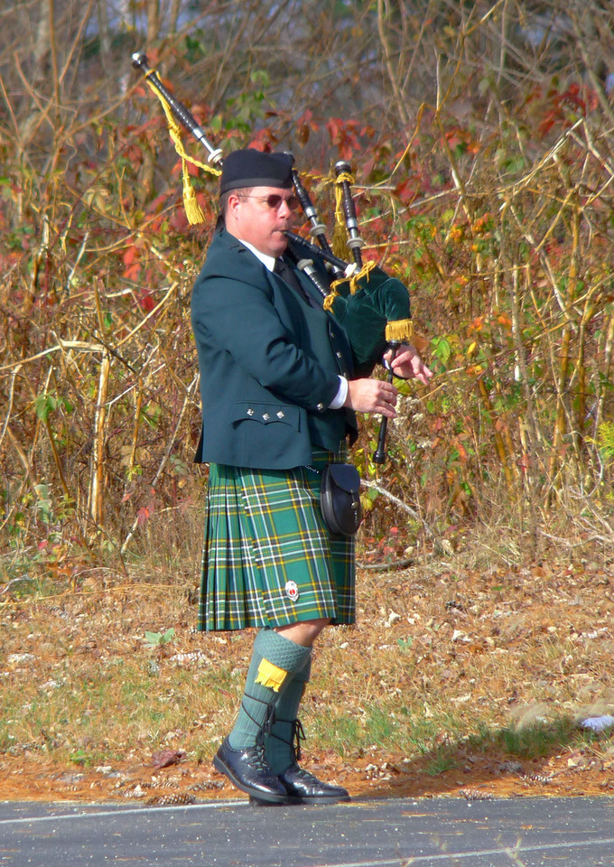 "Jack the Piper<br /> Lakeville lost one of it's older well-known citizens this past week. The family thought it fitting to have bagpipes playing in the background at the cemetery. I was at the library (getting a book called ""Seven Centuries of Paintings"", for all of you with inquiring minds) and when I came out with my large stack of books (ok, so I hit the knitting section, too), I could hear the bagpipes. He was playing right near where I was parked. After fumbling around with full arms and all, I managed to prop the camera up on another car and snap off a few pictures before he knew I was there, which I always like better. He had arrived early and was using the time and space to warm up before the funeral. Lucky me! I LOVE bagpipes!!!  When I got to my car, he stopped playing and we started talking. His wife of 27 years, Darlene, was with him and I just had the nicest time out in the sunshine talking with them. He was wishing he knew more about the man of whose funeral he was hired to play for and me being the ever curious one had my own questions...."