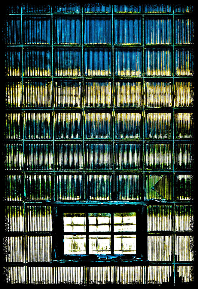 A little abstract fun for your Saturday enjoyment....<br /> This is a giant window at a water treatment plant. The panes of glass are double thick and vertically grooved. It has an interesting mix of reflective and translucent qualities. The top blue is the reflected sky. The golden color is a mix of  inside sunlight and reflected reeds at the water's edge (behind me). They were being illuminated by the setting sun. Then there's blue water and grass and finally the pavement I was standing on. The window is huge and because I was looking up at it, the image had every kind of distortion issue it could possible have. I brought it into lightroom and did the usual things to it but, I also really got to know what the transform tool can do ~miracles!