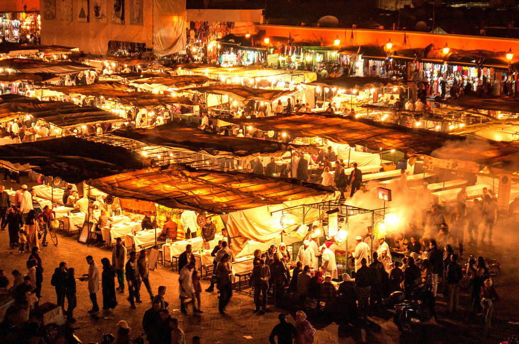 """M is for Marrakech Morocco.This is the Djemaa el Fna,    This plaza was the site of public executions, giving the name which means """"assembly of the dead.""""  There are water-sellers, henna artists, street entertainers during the day but at night it is spectacular.<br /> <br /> We sat at the Cafe de France and I propped my camera on the railing to get this shot."""
