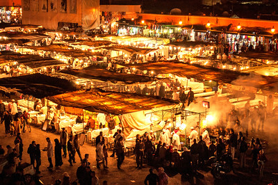 "M is for Marrakech Morocco.This is the Djemaa el Fna,    This plaza was the site of public executions, giving the name which means ""assembly of the dead.""  There are water-sellers, henna artists, street entertainers during the day but at night it is spectacular.  We sat at the Cafe de France and I propped my camera on the railing to get this shot."
