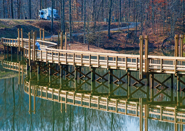 April 3 - Serenity - I went to take a picture of this curved bridge walkway at a state park and found someone relaxing and fishing from the bridge.  I assumed the RV in the background was his.<br /> <br /> Thanks for your comments on the bell tower image - they are much appreciated!