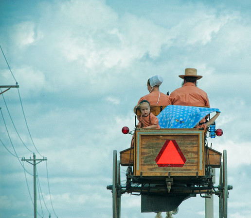 """Sept 12 - Amish Family<br /> <br /> There are two little girls in the back of the wagon, but  one was playing with her blue blanket in the wind.  I was taking the picture through the windshield while my husband was driving and the little girl never put the blanket down. <br /> <br />  The wagon was at the top of a hill about to go down the other side.  My vantage point was from the passenger side of a truck behind and below them on the hill.  This is why the wagon appears """"to be high"""".  I couldn't get the road in the shot because the truck's dash and hood was in the way.<br /> <br /> This was taken in Ohio around Millersburg, Charm, and Sugar Creek area.  I live about 2 hours away.<br /> <br /> Thanks so much for all your comments on the Amish images I have been posting these past few days!"""
