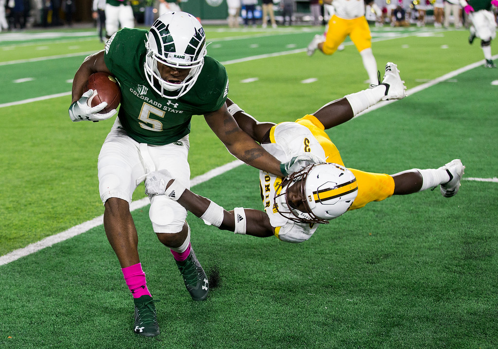 . Colorado State running back Marvin Kinsey, Jr., (5) tries to shed the tackle from Wyoming safety Alijah Halliburton (3) Friday evening Oct., 26 2018 at Canvas Stadium in Fort Collins. The Cowboys beat the home-team Rams 34-21. (Michael Brian/For the Reporter-Herald)