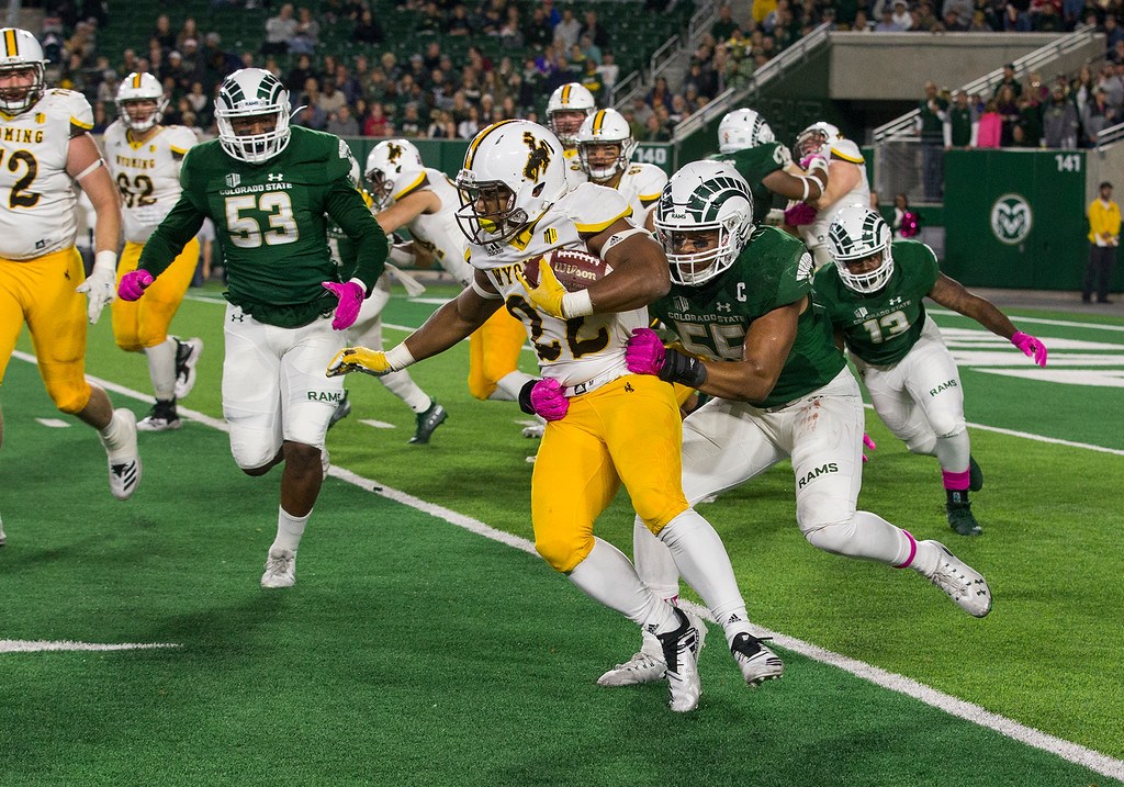 . Colorado State linebacker Josh Watson (55) trie to tackle Wyoming running back Nico Evans (22) Friday evening Oct., 26 2018 at Canvas Stadium in Fort Collins. (Michael Brian/For the Reporter-Herald)