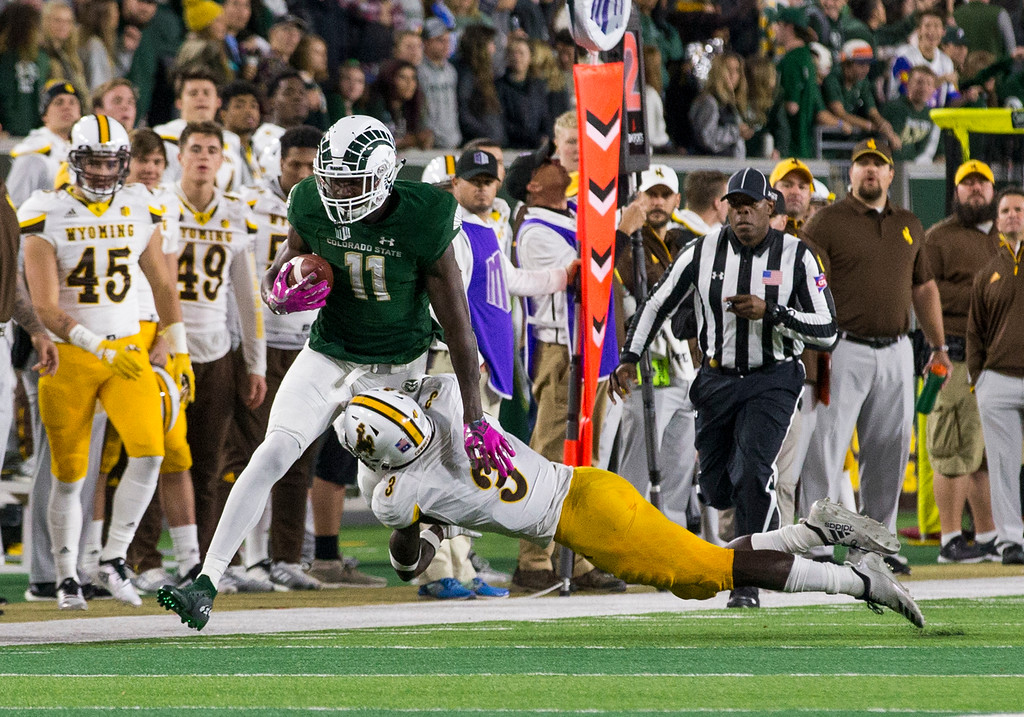 . Colorado State wide receiver Preston Williams (11) gets caught along the sideline by Wyoming safety Alijah Halliburton (3) Friday evening Oct., 26 2018 at Canvas Stadium in Fort Collins. (Michael Brian/For the Reporter-Herald)