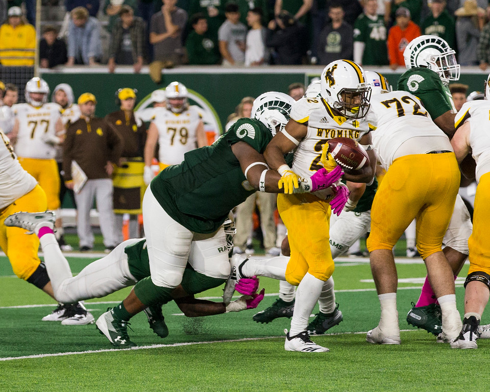 . Colorado State defensive lineman Devin Phillips (94) strips the ball from Wyoming running back Nico Evans (22) Friday evening Oct., 26 2018 at Canvas Stadium in Fort Collins. (Michael Brian/For the Reporter-Herald)