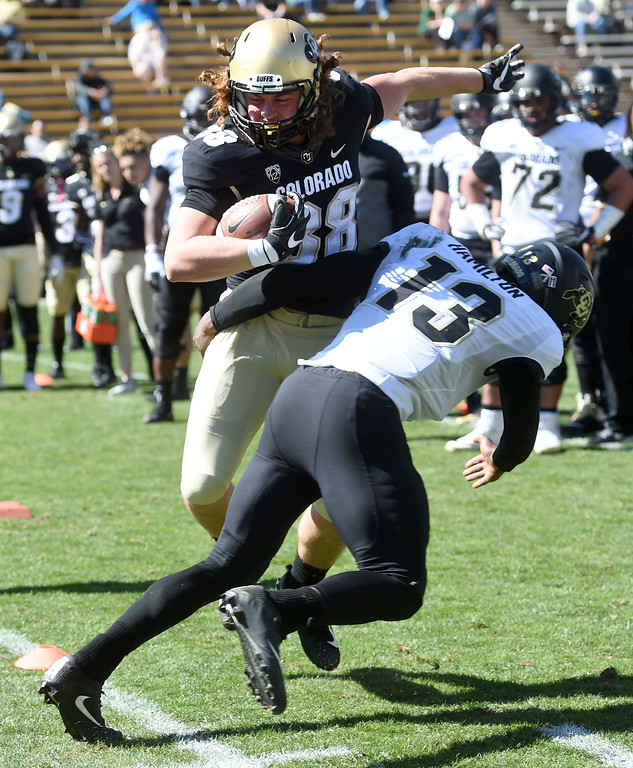 . Brady Russell avoids the tackle of Shamar Hamilton during the CU Spring football festivities on Saturday.  Cliff Grassmick  Photographer  March 17, 2018